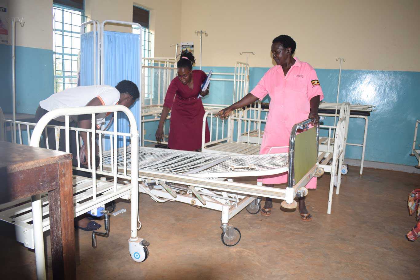 IDIWA Staff being shown an adjustable bed in the labour ward by midwife Mbulamuti HC III